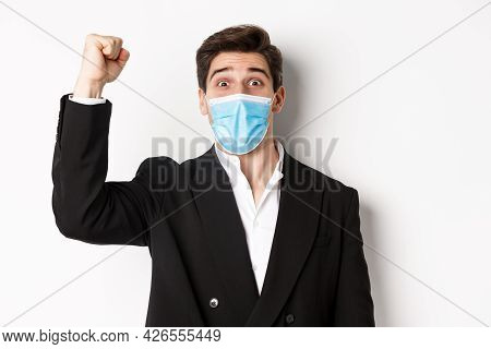 Concept Of Covid-19, Business And Social Distancing. Close-up Of Excited Businessman In Medical Mask
