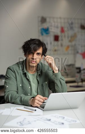 Stylish Fashion Designer Looking At Camera While Sitting Near Laptop In Atelier