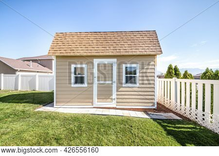 Shed At A Backyard With Roof Shingles And Vinyl Wall Siding