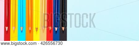 A Set Of Colored Pencils On A Colorful Background. A Group Of Wooden Colored Pencils For Drawing. Br