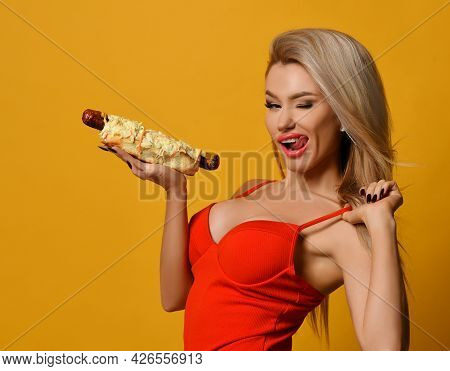 Sexy Blonde Woman Winks Seductively Looking At The Camera And Holding Fast Food. Glamorous Beautiful