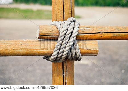 Close-up Fragment Of Wooden Fence. Wooden Logs Tied With Strong Rope. Decorative Knot Element.