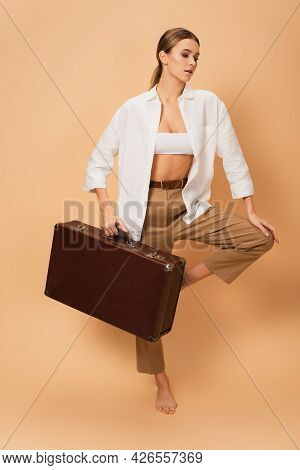 Trendy Woman In Trousers And White Shirt Standing On One Leg With Retro Suitcase On Beige Background