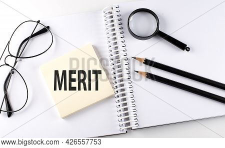 Text Merit On Sticker With Keyboard , Pencils And Office Tools