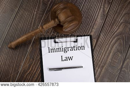 Immigration Law Text On The Paper With Gavel On The Wooden Background