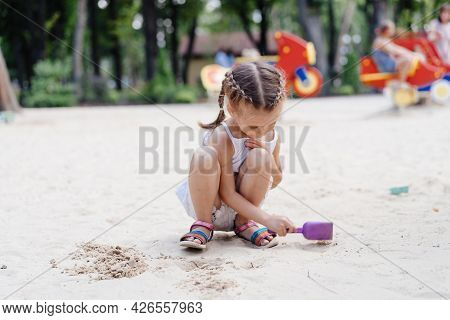 Little Girl Playing Sandbox Playground Digging Sand Shovel Building Sand Figure Summer Day. Caucasia