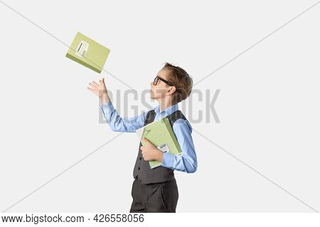 Caucasian Schoolboy Teen In Classroom On White Background With Notebooks In Hand. One Notebook The B