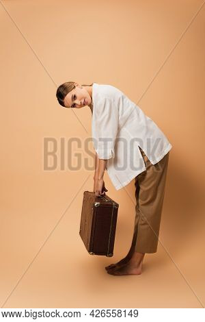 Barefoot Woman In Trousers And White Shirt Bending With Retro Suitcase On Beige Background