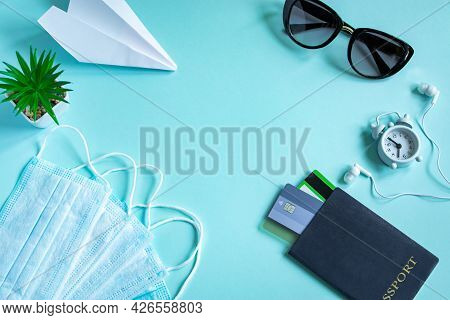 Safe Travel Concept During The Coronavirus Pandemic. Passport, Medical Mask And Sun Glasses On A Blu