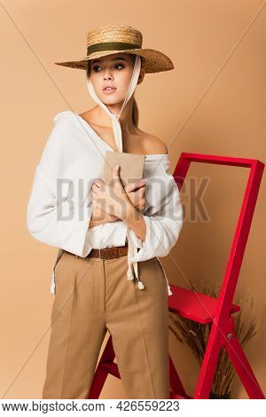 Young Woman In White Shirt, Trousers And Straw Hat Holding Book On Beige Background