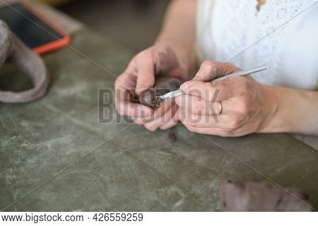 Artisan Pottery Tutor. Womens Hands Shake A Piece Of Gray Clay. Pottery Made Of Clay With Their Own