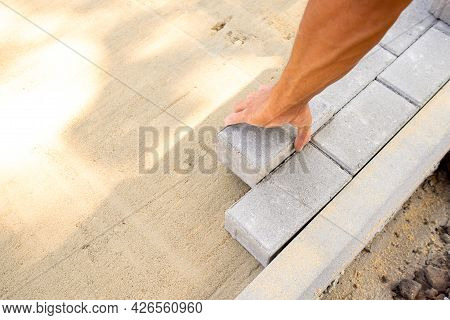 Bricklayers Hand Lays Paving Slabs In Prepared Sand Mixture. Process Of Laying Sidewalk, Landscaping