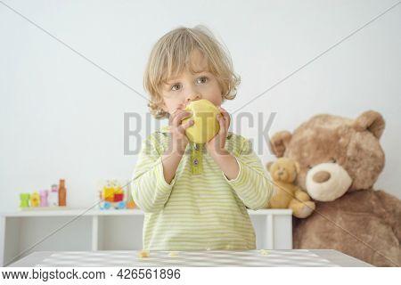 Cute Happy Child Boy Having Fun Eating A Big Fresh Yellow Apple Fruit At Home. Children Healthy Eati