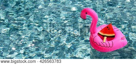 Watermelon Slice Popsicle On Inflatable Of Pink Flamingo Ring Floating In Swimming Pool