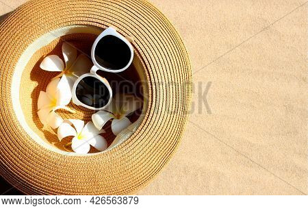 Summer Hat With Sunglasses And Plumeria Flowers On Sand