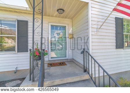 Facade Of Home On Real Estate Listing With Storm Door And Glass Pened Front Door