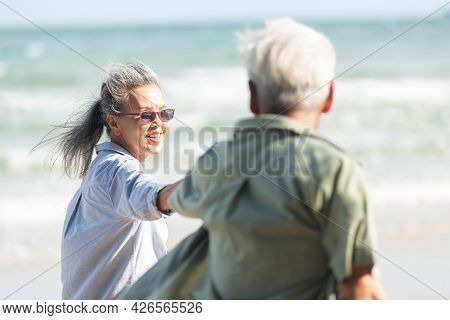 Happy Asian Senior Man And Woman Couple Holding Hands Walking To The Beach Sunny With Bright Blue Sk