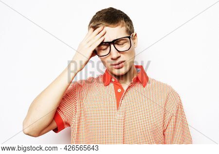 Young handsome man with glasses over isolated background suffering from headache desperate