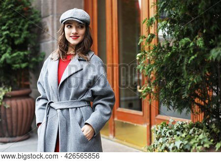 Lifestyle and people concept: Outdoor portrait of yong beautiful happy smiling woman wearing stylish hat, coat.