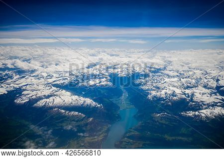 Switzerland - 05.29.2015 - View From The Airplane Window, Swiss Alps. Mountains, Snow, Clouds.