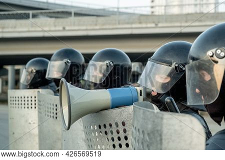 Policeman in riot helmet standing among coworkers with riot shields and speaking into mefaphone while neutralizing terrorists