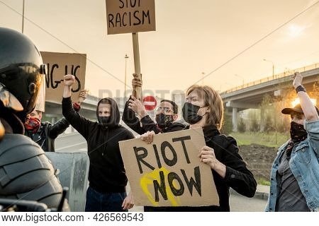 Group of disgruntled people in masks with signs claiming equal rights for all ethnicities while screaming against riot police on road
