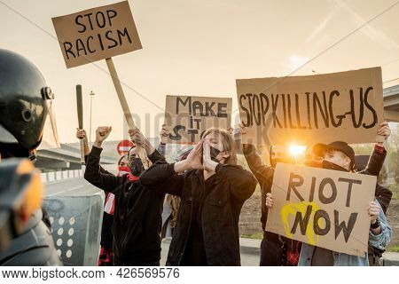 Group of angry activists in masks holding signs and sreaming while participating in rally in protest of racism