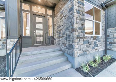 Home Facade With Stone Brick Wall And Gray Front Door With Frosted Glass Panels