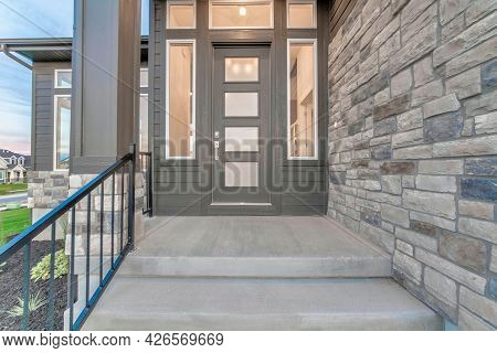 Front View Of The House Entrance With Glass Panelled Front Door And Sidelights