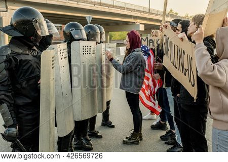 Young woman in hood standing in front of police guards and giving daisy to them while trying to stop violence between police and protestors