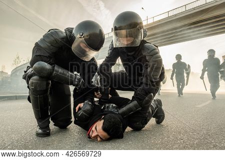 Strong riot policeman in helmets twisting arms of protester behind his back while arresting him on street