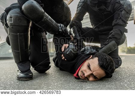 Riot force in protective wear pressing middle eastern man to ground while rresting him during rally