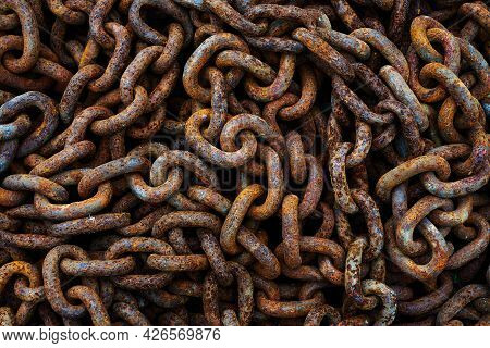 A Pile Of Rusty Chains As A Dark Textured Background. Dark And Rusted Chain Showing The Texture Of R