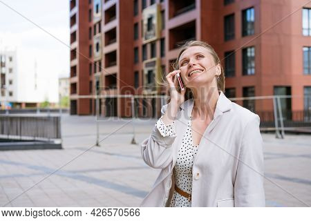 Successful Woman Talking On The Phone Walking Down The Street. Portrait Of A Stylish Smiling Busines