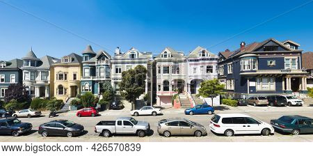 SAN FRANCISCO, CALIFORNIA, USA - APRIL 29, 2015: Painted Ladies houses seen from Alamo Square in San Francisco with cars parked in front of them. Panoramic photo