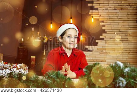Amazing Child In Santa Claus Cap On Blurred Golden Background With Lights. Christmas Time, Atmospher