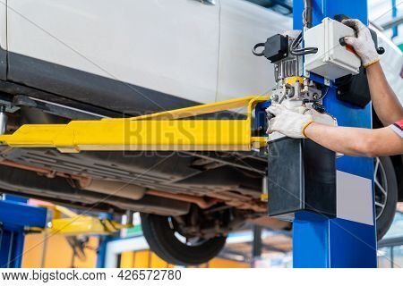 Hand Of Auto Mechanic Using A Car Lift In Car Repair Service Centre Background