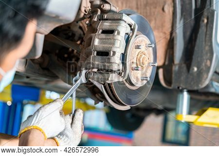Car Mechanic Checking A Disc Brake Of The Vehicle For Repair, In Process Of New Tire Replacement. Ca