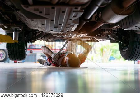 Mechanic In Uniform Lying Down And Working Under Car At Auto Service Garage, Car Mechanic Adjusting