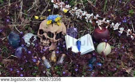 Beltane Ritual With Skull, Open Book Of Spells, Crystals And Flowers Outside.  Esoteric, Gothic And