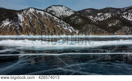 Cracks And Blocks Of Hummocks Are Visible On The Ice Of The Frozen Lake. The Coastal Mountains Are C