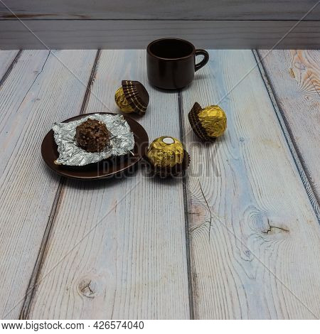 There Is A Brown Porcelain Cup And Saucer On The Wooden Table. There Is An Unwrapped Chocolate Candy