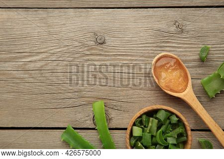 Aloe Vera Gel On Wooden Spoon With Aloe Vera On Grey Wooden Background. Top View.