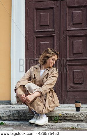 Young Millennial Woman With Wild Hair Dressed In An Autumn Coat Sitting Near The Door Of An Old Buil