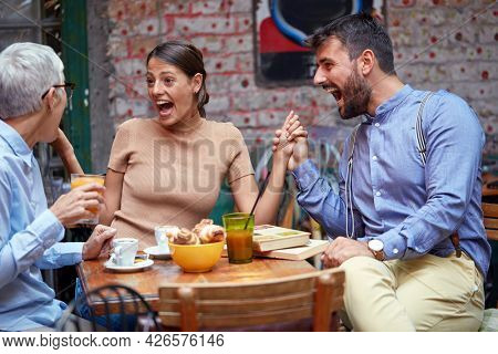 different age and gender people socializing, looking surprised with mouth open, laughing, holding hands