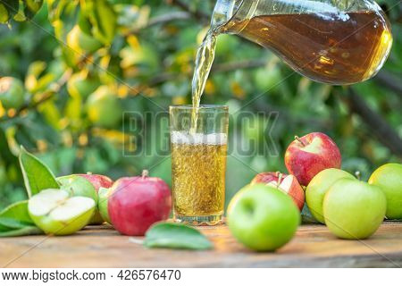 Pouring apple juice into the glass. Fresh organic apples and glass of apple juice on wooden table in the summer orchard garden.