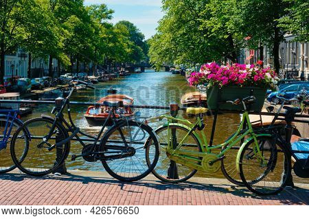 Typical Amsterdam view - Amsterdam canal with boats and bicycles on a bridge with flowers. Amsterdam, Netherlands