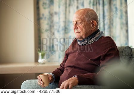 Depressed senior man sitting on armchair holding disposable cup of coffee and thinking. Frustrated retired man sitting on sofa. Sad mature man sitting alone at nursing home with sad expression.