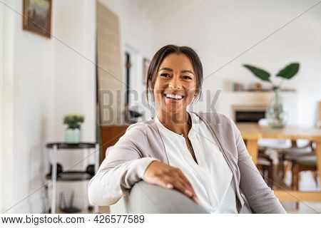 Happy mature woman relaxing on her couch at home in the living room. Beautiful young woman laughing alone in living room. Beautiful smiling african lady sitting on sofa.