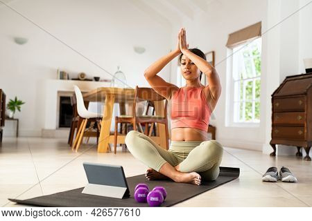 Mature woman sitting on yoga mat and looking at digital tablet for online lessons of hata yoga. Healthy mid adult black woman practicing yoga with online trainer at home. African lady practicing yoga.